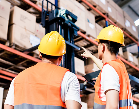 two men standing in a warehouse with hard hats and orange vests staring at boxes on shelves and one is pointing at one of the boxes,